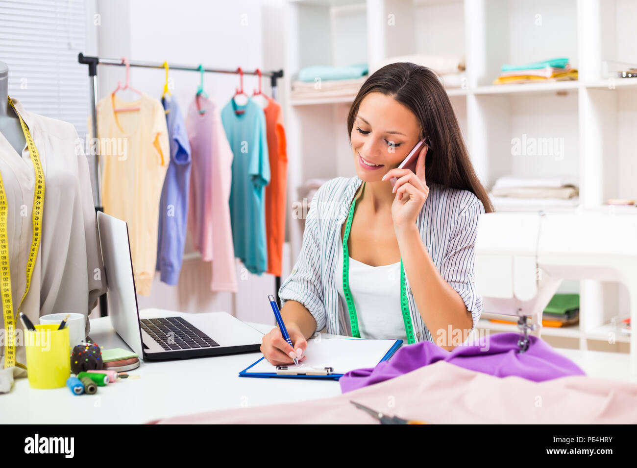 Beautiful seamstress using phone and working at her workshop. - Stock Image