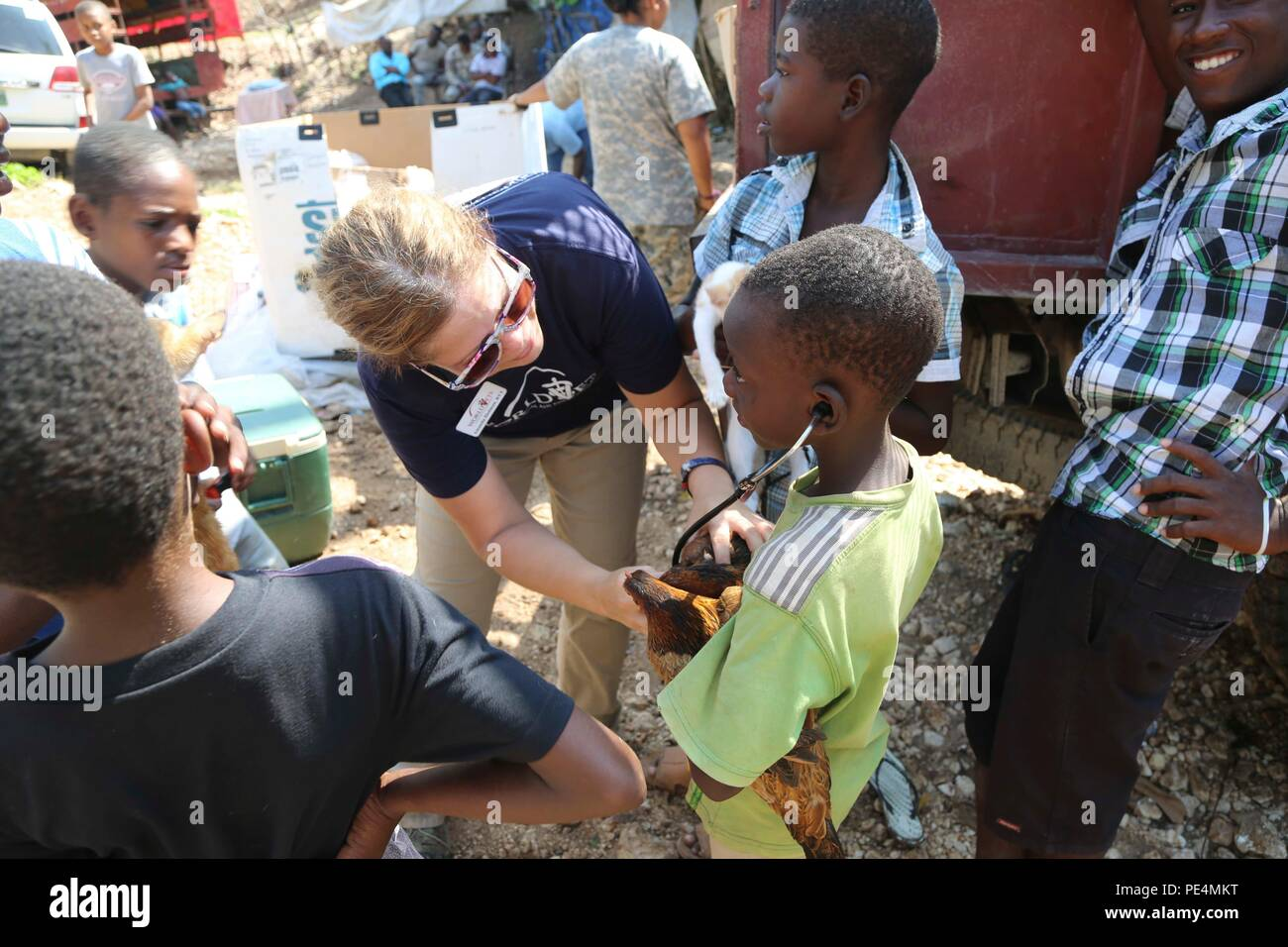 150917-A-BK746-197 PORT AU PRINCE, Haiti (Sept. 17, 2015)  A volunteer with the non-governmental organization (NGO) World Vets shows a child how a stethoscope works during a veterinary civil affairs program in support of Continuing Promise 2015 (CP-15). World Vets volunteers are working alongside other NGOs and military members during CP-15. Continuing Promise is a U.S. Southern Command-sponsored and U.S. Naval Forces Southern Command/U.S. 4th Fleet-conducted deployment to conduct civil-military operations including humanitarian-civil assistance, subject matter expert exchanges, medical, denta - Stock Image