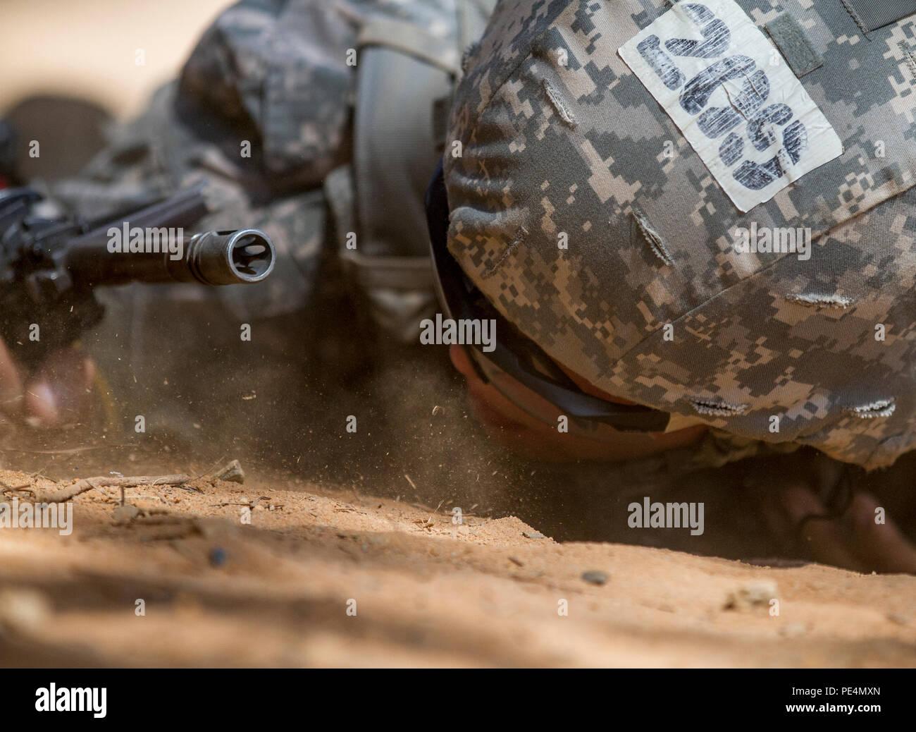 A U.S. Army Soldier low crawls through an obstacle on a buddy team live fire lane during the seventh week of basic training at Fort Jackson, S.C., Sept. 19, 2015. (U.S. Army photo by Sgt. Ken Scar) - Stock Image