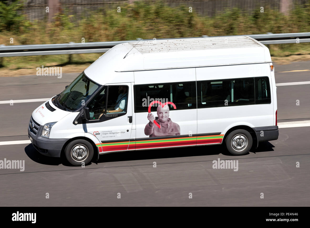 AWO minibus on motorway. AWO is one of the top six associations of the free welfare in Germany. - Stock Image