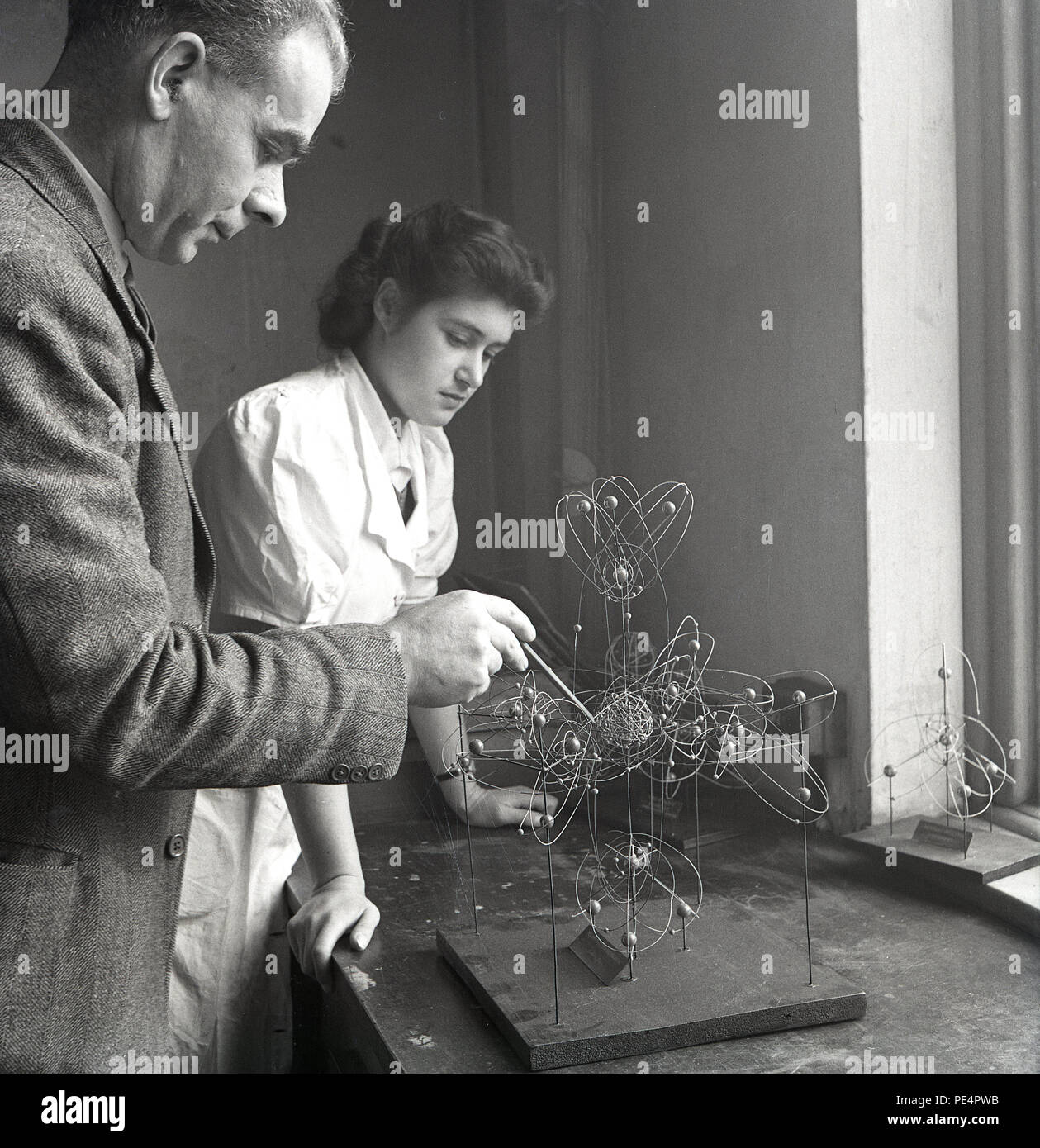 1950s, male university professor teaching the science of physics to a femlale student using a penceil and a metal atom model on a wooden base sat on a workbench, England, UK. - Stock Image
