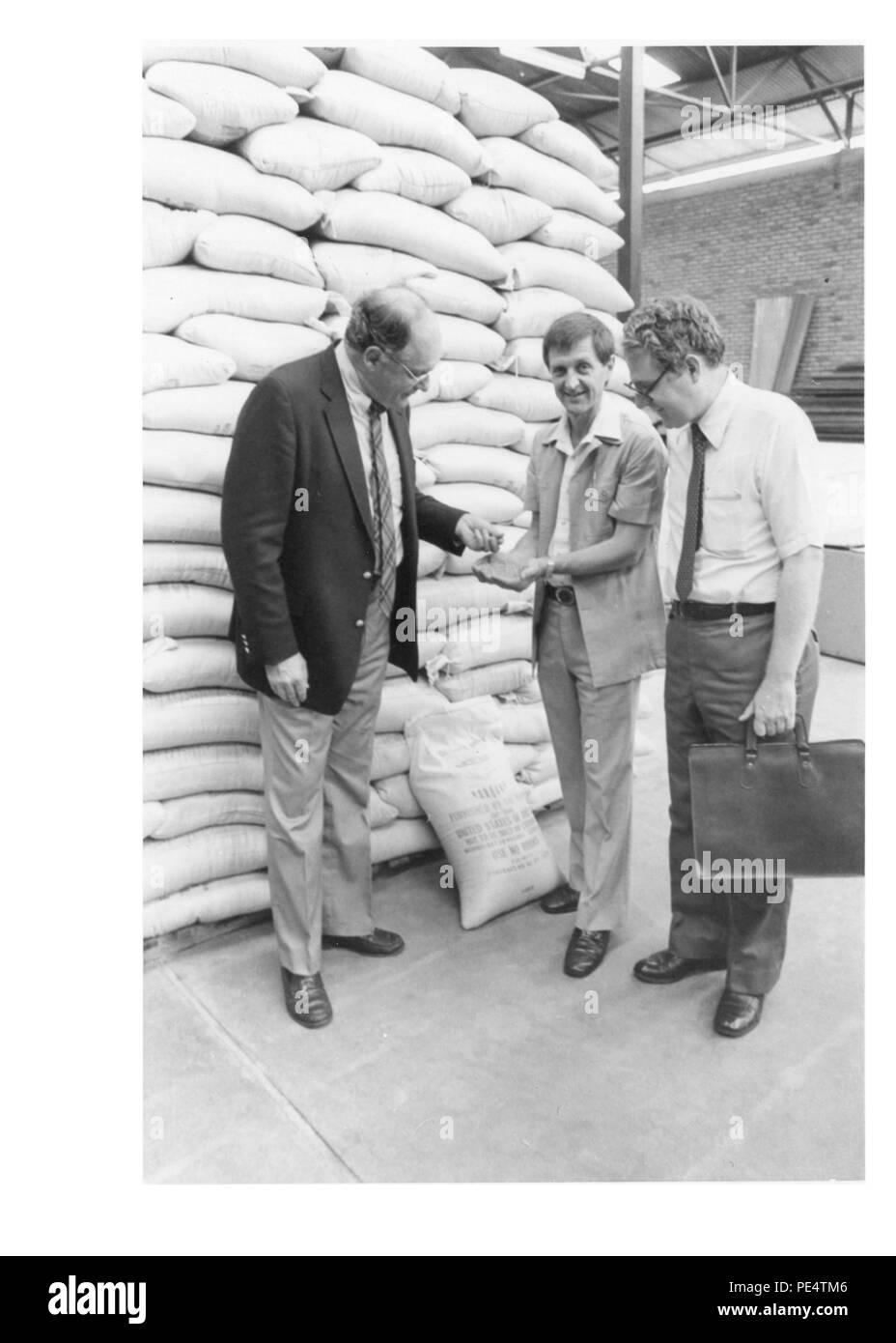 Food for Work in Rwanda - 1983 - American Ambassador John Blane and DCM Donald Hester examine USAID food stocked in ADRA warehouse in Kigali. - Stock Image