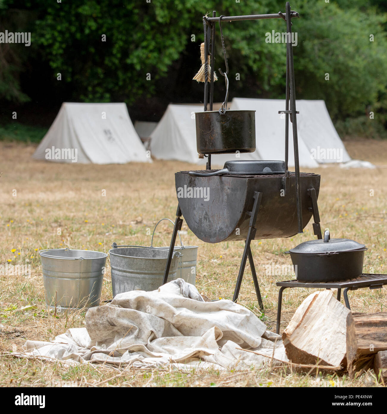 Buckets iron skillets and pans and a wood stove on dry grass and vintage kitchen utensils suggesting a Civil War or gold rush c& with canvas tent & Buckets iron skillets and pans and a wood stove on dry grass and ...
