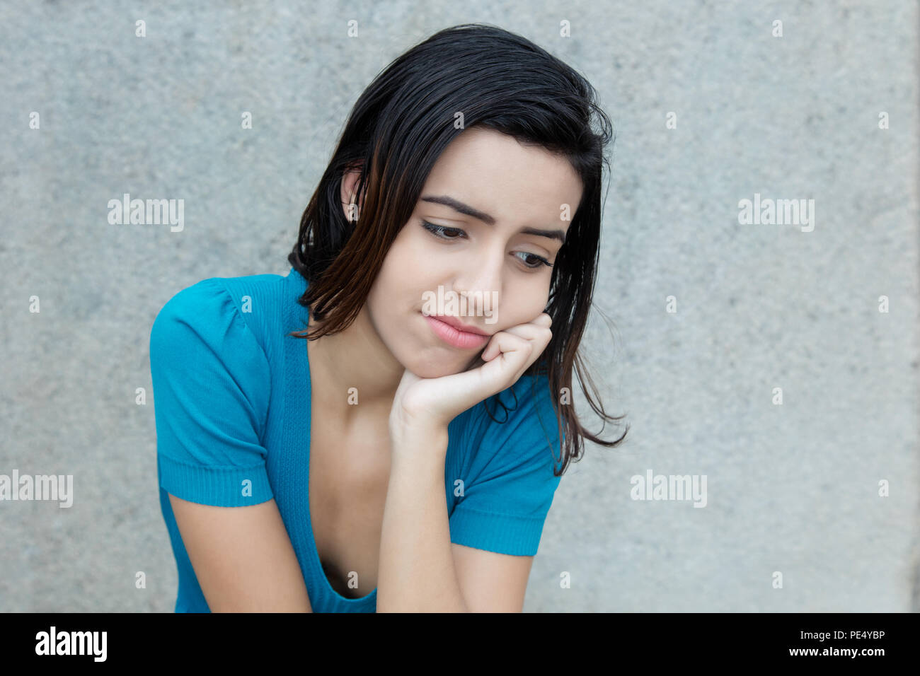 Bullied latin american young adult woman outdoors with copy space - Stock Image