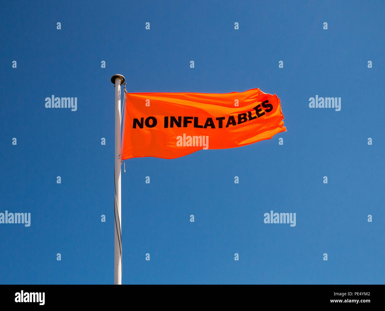 Colour image of an orange flag with NO INFLATABLES in black letters on a metal flagpole, shot from below against a clear blue sky - Stock Image
