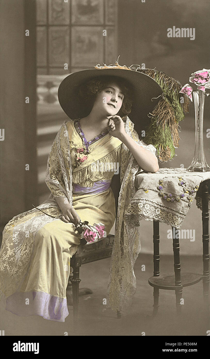Vintage, hand-tinted, sepia, Edwardian postcard showing a beautiful woman in a picture hat. - Stock Image