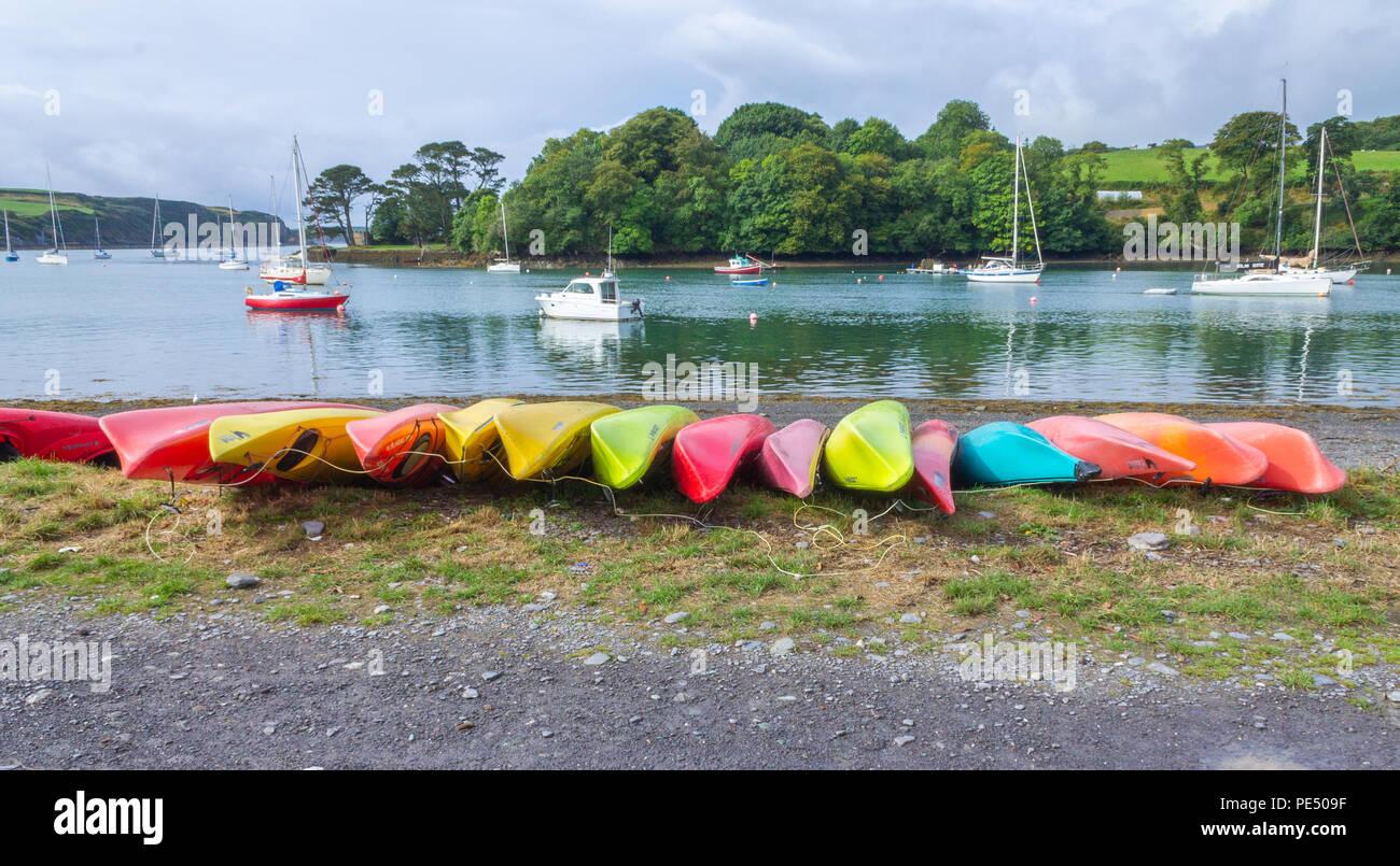 rows of plastic kayaks upturned on a pebble beach, West Cork, Ireland - Stock Image