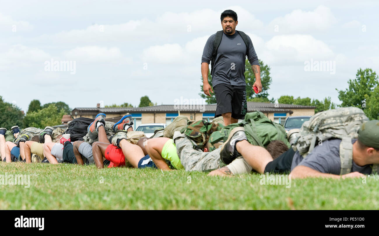 Chris Stokes, GORUCK Light qualified cadre, standing, instructs 31 participants on a team pushup challenge Sept. 25, 2015, on Dover Air Force Base, Del. During the five-hour-long GORUCK Light team cohesion challenge, Stokes, a former U.S. Marine Corps reconnaissance member, presented Team Dover members with numerous physical challenges along a 7.8-mile course as they learned to overcome adversity by working as a team. (U.S. Air Force photo/Roland Balik) - Stock Image