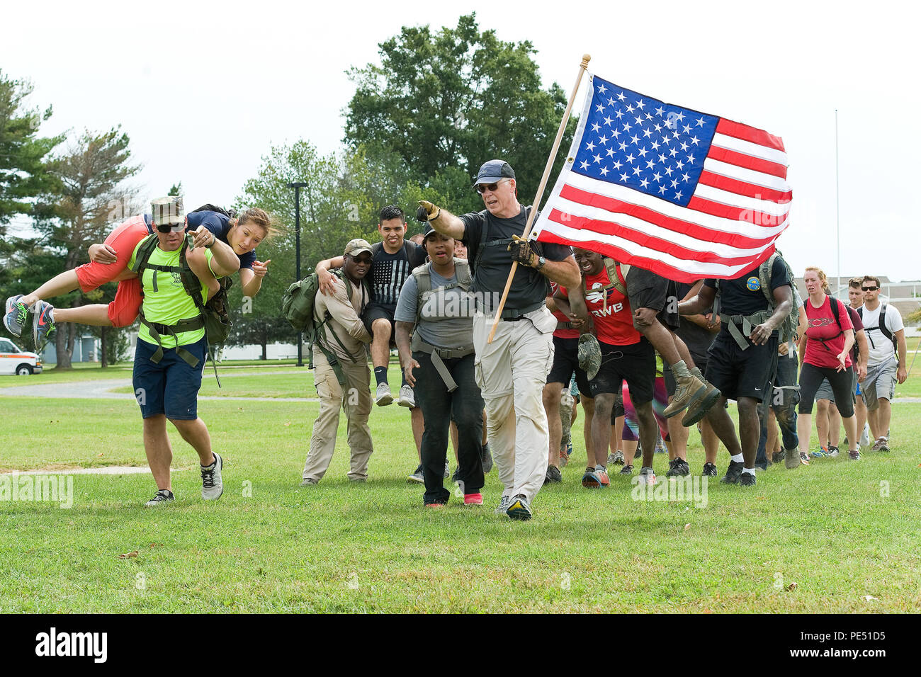 Master Sgt. Gary Porter, 512th Maintenance Squadron C-17 avionics intermediate maintenance section chief, carries the U.S. flag as he leads fellow GORUCK Light Team Dover members to a simulated extraction point Sept. 25, 2015, on Dover Air Force Base, Del. During the five-hour-long challenge led by a former U.S. Marine Corps reconnaissance member, participants completed numerous physical challenges along a 7.8-mile course and learned to overcome adversity by working as a team. (U.S. Air Force photo/Roland Balik) - Stock Image