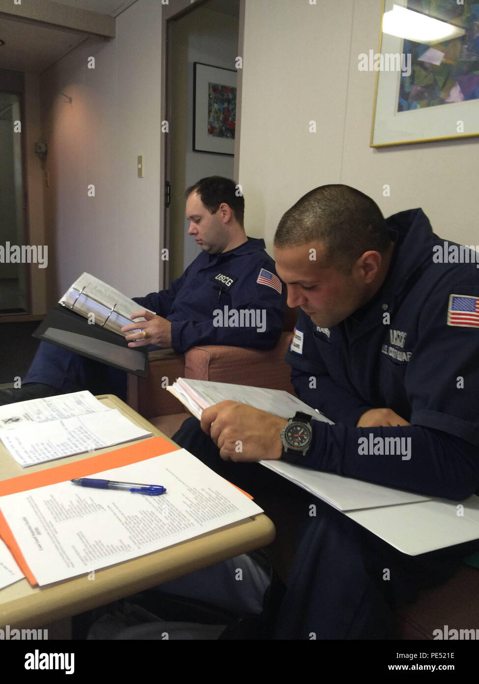 Lt. Peter Raneri and Lt. Matt Arnold, port state control officers at Coast Guard Activities Far East, examine documentation aboard the 656-foot U.S. flagged vehicle carrier ship, Green Lake, at Yokosuka Shinko Port wharf in Yokosuka City, Japan, Sept. 29, 2015. Coast Guardsmen conduct inspections to ensure a vessel has a suitable structure, correct documentation, proper working equipment and lifesaving equipment and adequate accommodations. (U.S. Coast Guard photo by Lt. Kenn Yuen/Released) - Stock Image