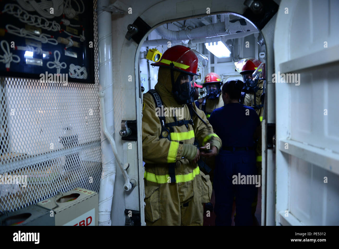 Seaman Bryce Kachinski and fellow new crew members of the Coast Guard Cutter Midgett, a 378-foot high-endurance cutter homeported in Seattle, prepare for shipboard fire training during a patrol in the Pacific Ocean, Oct. 8, 2015. Firefighting and other damage control emergency situations are some of the first things taught to new crew members. (U.S. Coast Guard photo by Petty Officer 1st Class Levi Read) Stock Photo