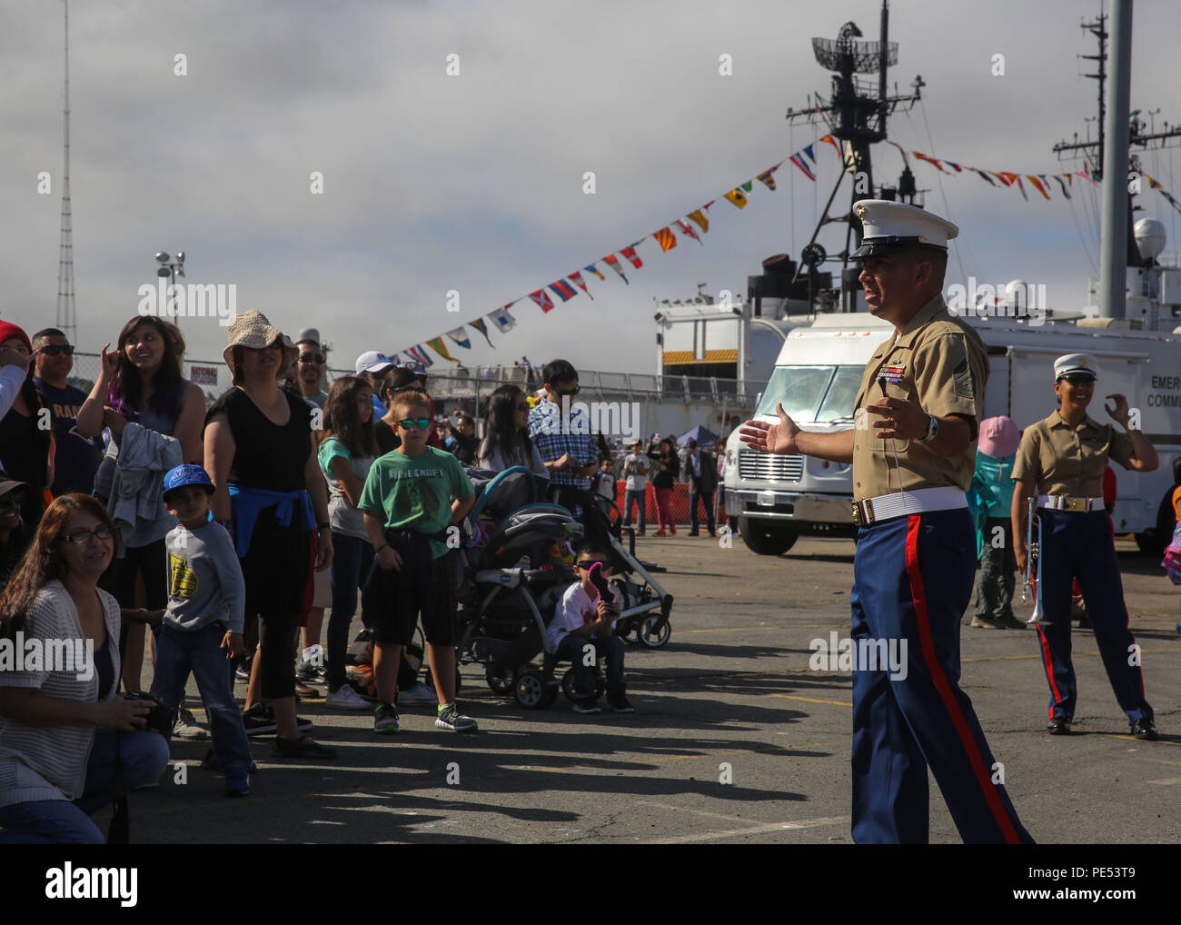 Gunnery Sergeant Tracy Martinez, conductor, 1st Marine Divison Band, welcomes guests to a static ship display on Pier 80 as part of San Francisco Fleet Week 2015, Oct. 10. SFFW 15' is a week-long event that blends a unique training and education program, bringing together key civilian emergency responders and Naval crisis-response forces to exchange best practices focused on humanitarian assistance disaster relief with particular emphasis on defense support to civil authorities. - Stock Image