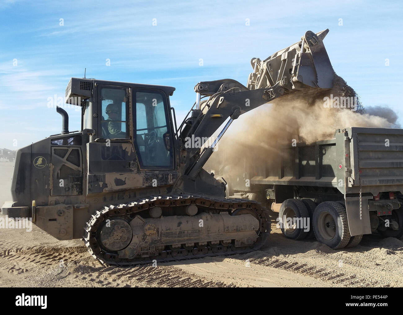 151002-N-QB788-541 SAN CLEMENTE ISLAND, Calif. (Oct. 02, 2015) Equipment Operator Constructionman Austin Keeler, from Florence, Colo., uses a tracked front end loader to dump three-quarter inch aggregate into a dump truck. The material is being transported to a stockpile located at the gate leading into the Shore Bombardment Area (SHOBA) which the road crew repair team will use for future road maintenance operations. (U.S. Navy photo by Equipment Operator 3rd Class Austin Wickham/Released) - Stock Image