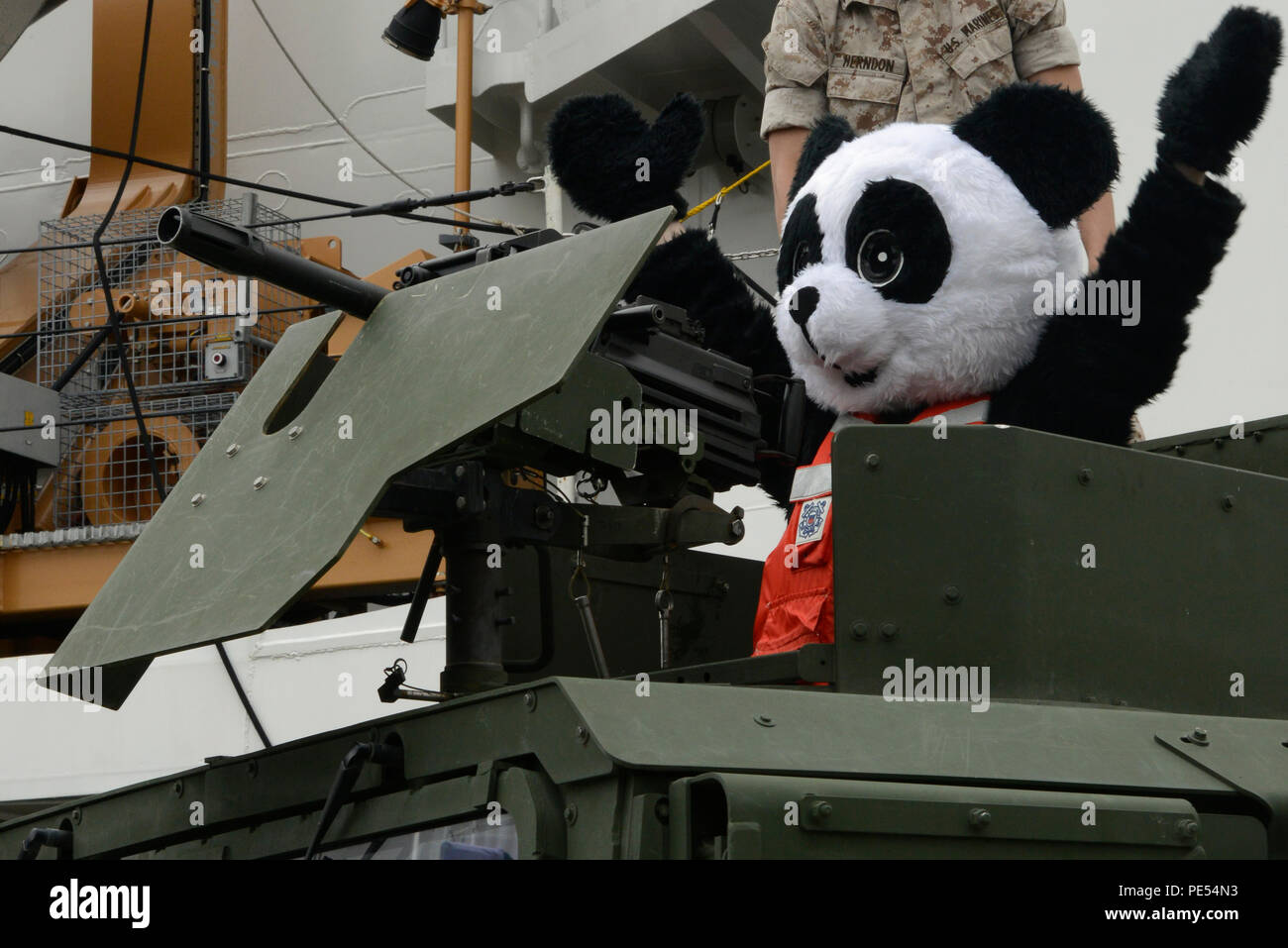 PFD Panda, the Coast Guard mascot used to bring attention to the use of personal flotation devices, pops out of the top of a High Mobility Multipurpose Wheeled Vehicle, supplied by members from the Marine Corps Security Forces Battalion from Naval Base Kitsap-Bangor, during a Seattle Seahawks change-of-command ceremony at Coast Guard Base Seattle, Oct. 13, 2015. During the ceremony, various vehicles, boats and cutters were on display and available for tours to attendees who were representing the Coast Guard 13th District, MCSF Battalion Bangor, Seahawks, Sea Gals and USAA. (U.S. Coast Guard ph - Stock Image