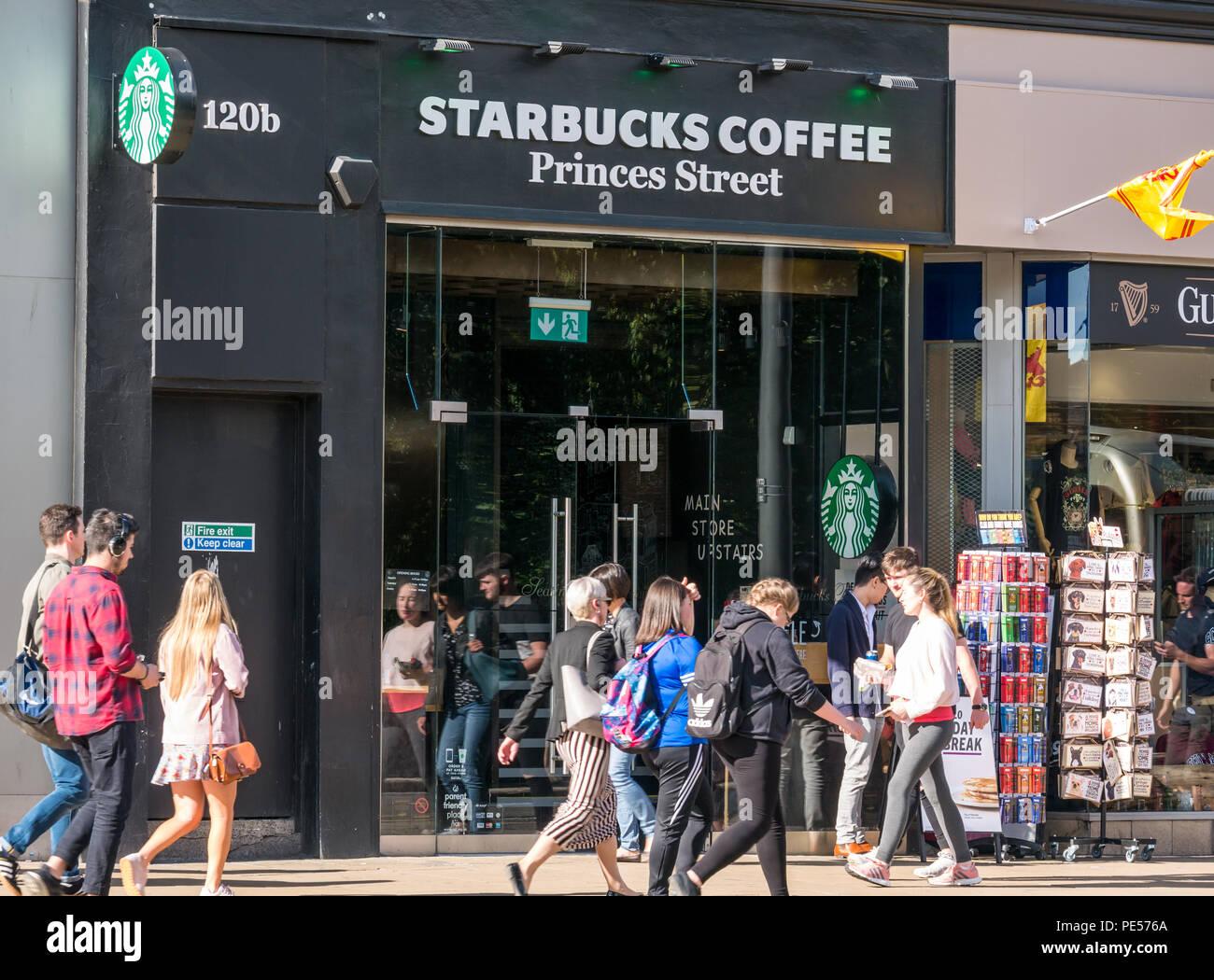People Walking Past Frontage Of Starbucks Coffee Shop