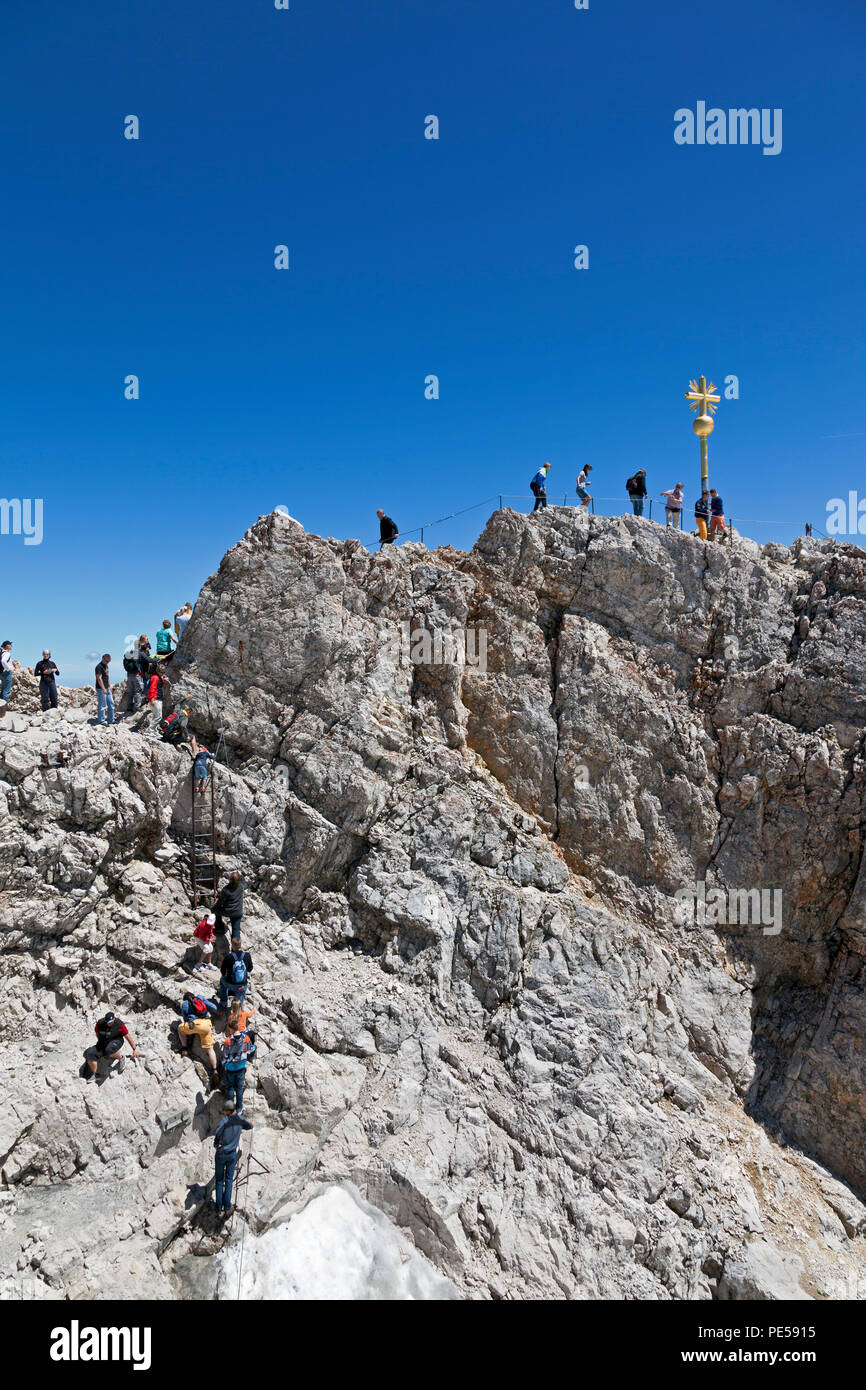 Tourists climbing to the Golden Cross - the highest point in Germany on the summit of Zugspitze at 2,962 m above sea level Stock Photo