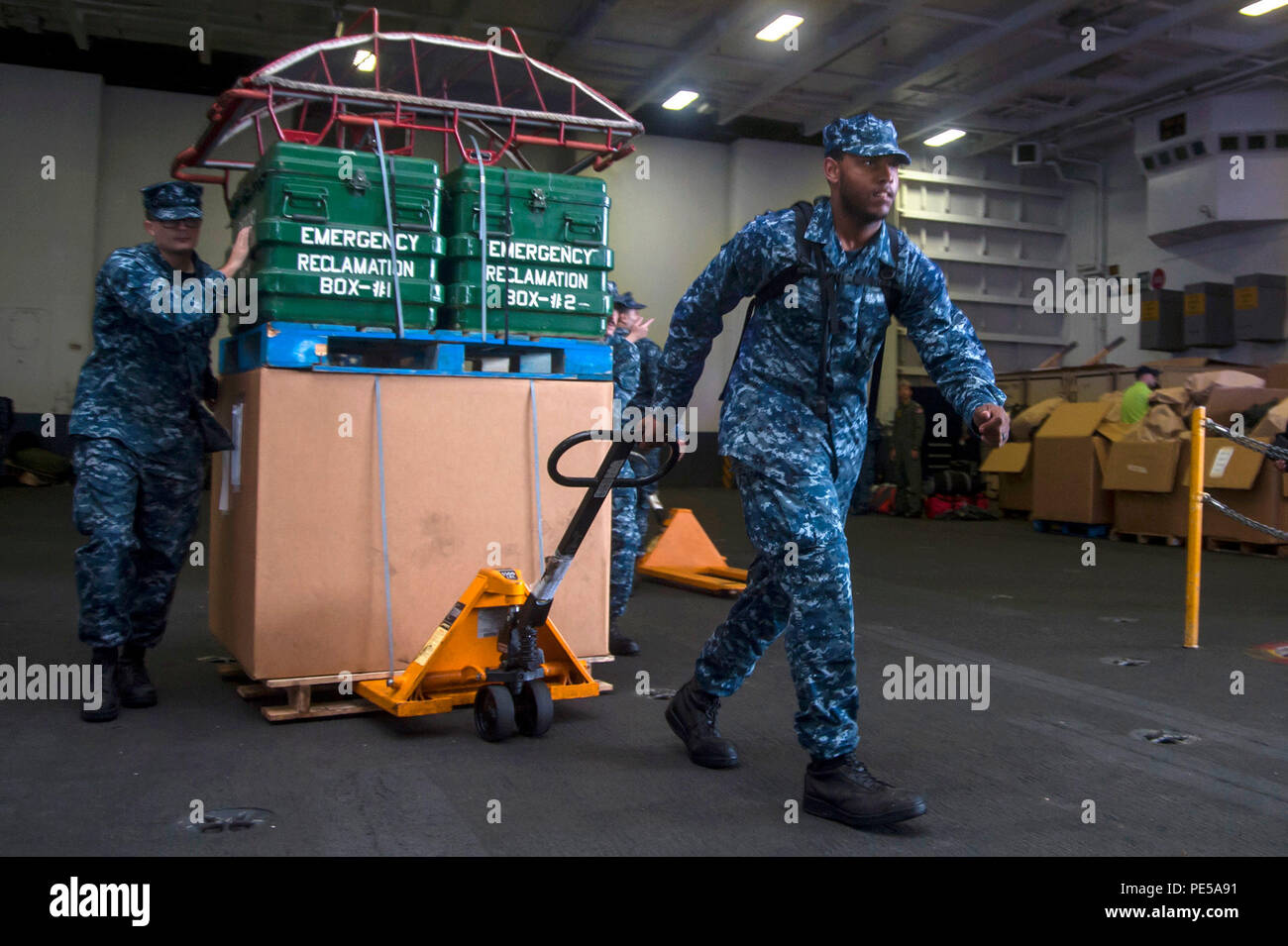 """151001-N-QH848-007 NORFOLK (Oct. 1, 2015) Aviation Electrician's Mate 3rd Class D. Fuger, left, and Aviation Machinist's Mate Airman D. Dolloson, assigned to the """"Fist of the Fleet"""" of Strike Fighter Squadron (VFA) 25, move equipment through the hangar bay of aircraft carrier USS Harry S. Truman (CVN 75). Truman is at sea to sortie in response to Hurricane Joaquin. (U.S. Navy photo by Mass Communication Specialist 3rd Class A. A. Cruz/Released) Stock Photo"""