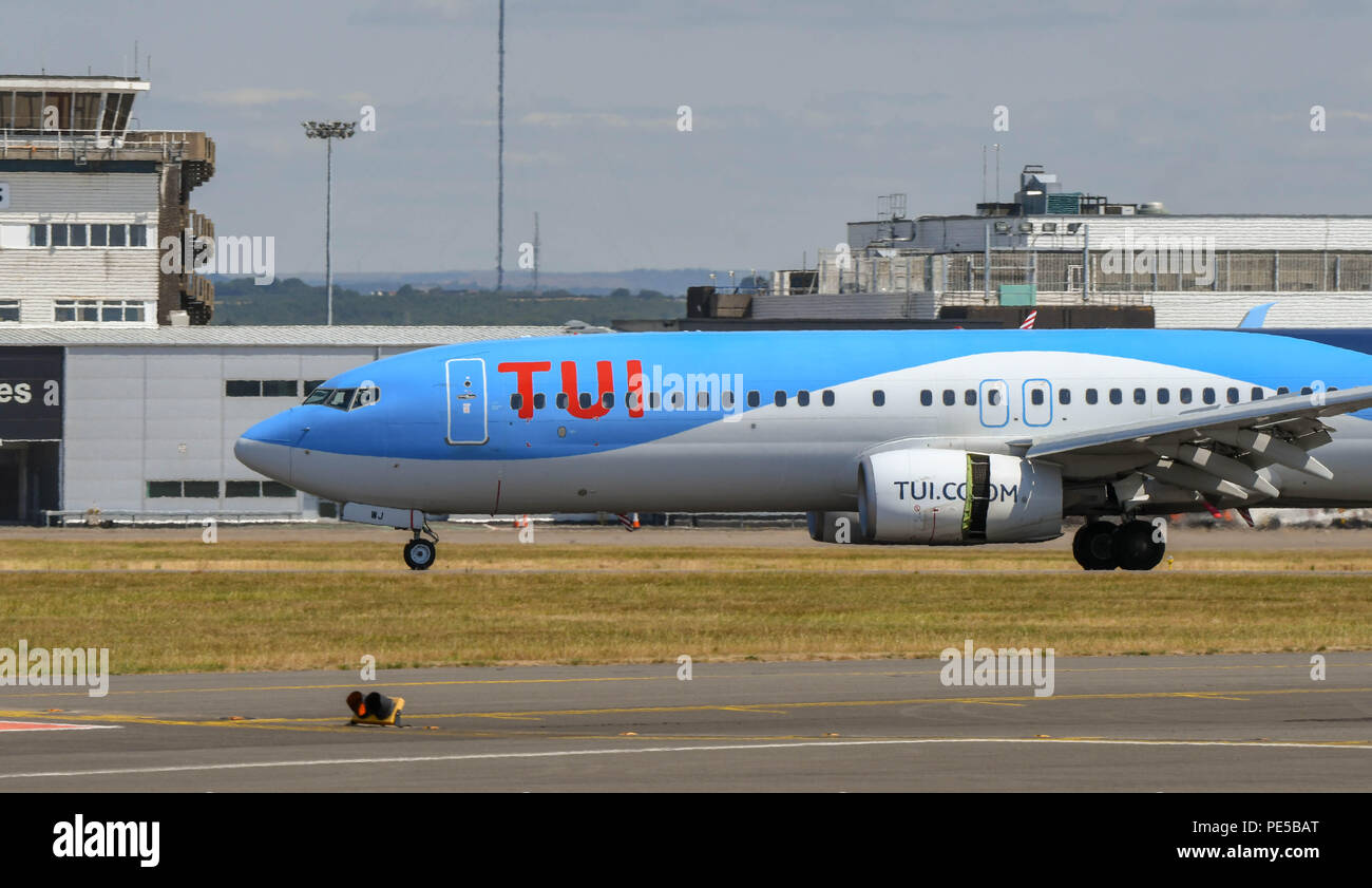TUI Boeing 737 landing at Cardiff Wales Airport. The thrust reverser flap on the engine is open to help the aircraft to slow down - Stock Image