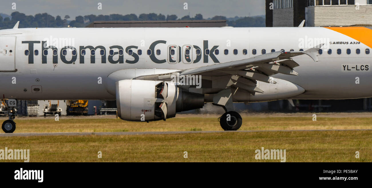 Close up view of a Thomas Cook Airlines Airbus A320 jet landing at Cardiff Wales Airport. The thrust reverser flaps on the engine are open. - Stock Image