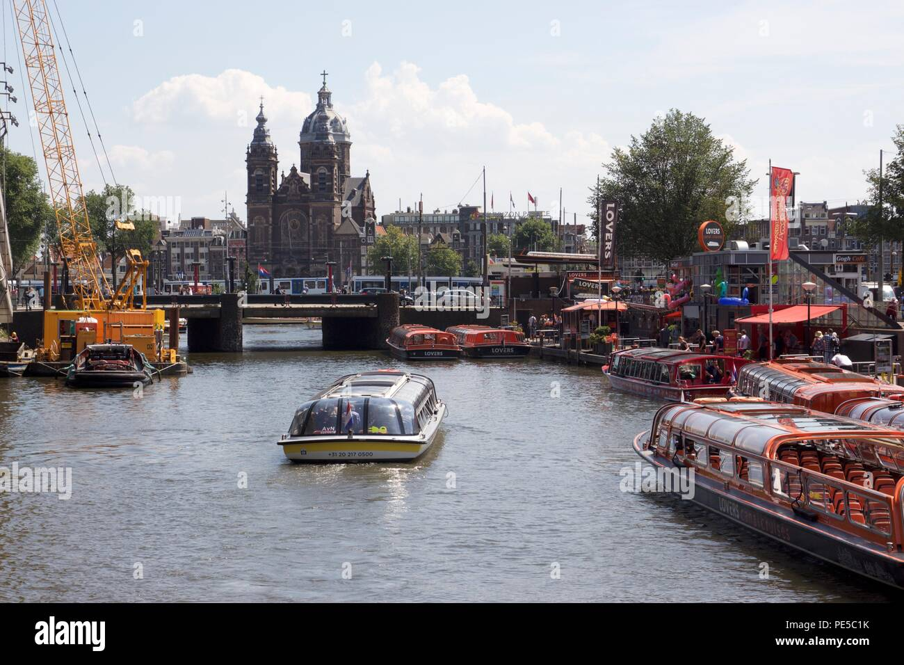 Numerous tourist boats on the river IJ in Central Amsterdam, the Netherlands - Stock Image