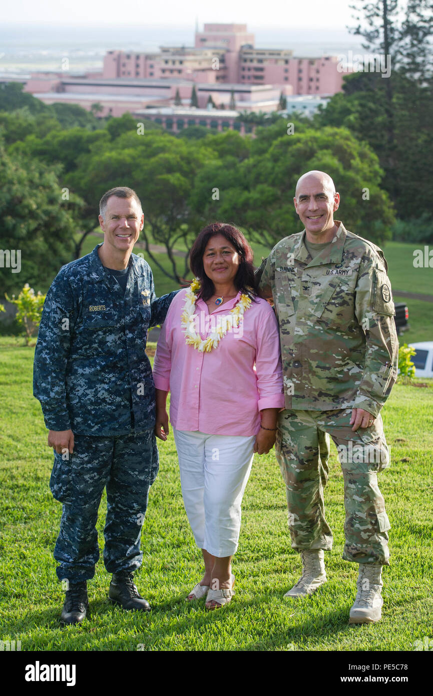Anita Clingerman, center, Tripler Fisher House manager, poses with U.S. Army Col. David K. Dunning, right, Commander of Tripler Army Medical Center and U.S. Navy Capt. Peter F. Roberts, left, TAMC Deputy Commander for Clinical Services, during a volunteer appreciation event at the Tripler Fisher House Sept. 25, at TAMC, Hawaii. The Fisher House Foundation is best known for its network of comfort homes where military and veteran's families can stay at no cost while a loved one is receiving medical treatment at major military and VA medical facilities. The Tripler Fisher House is one of 65 Fishe - Stock Image