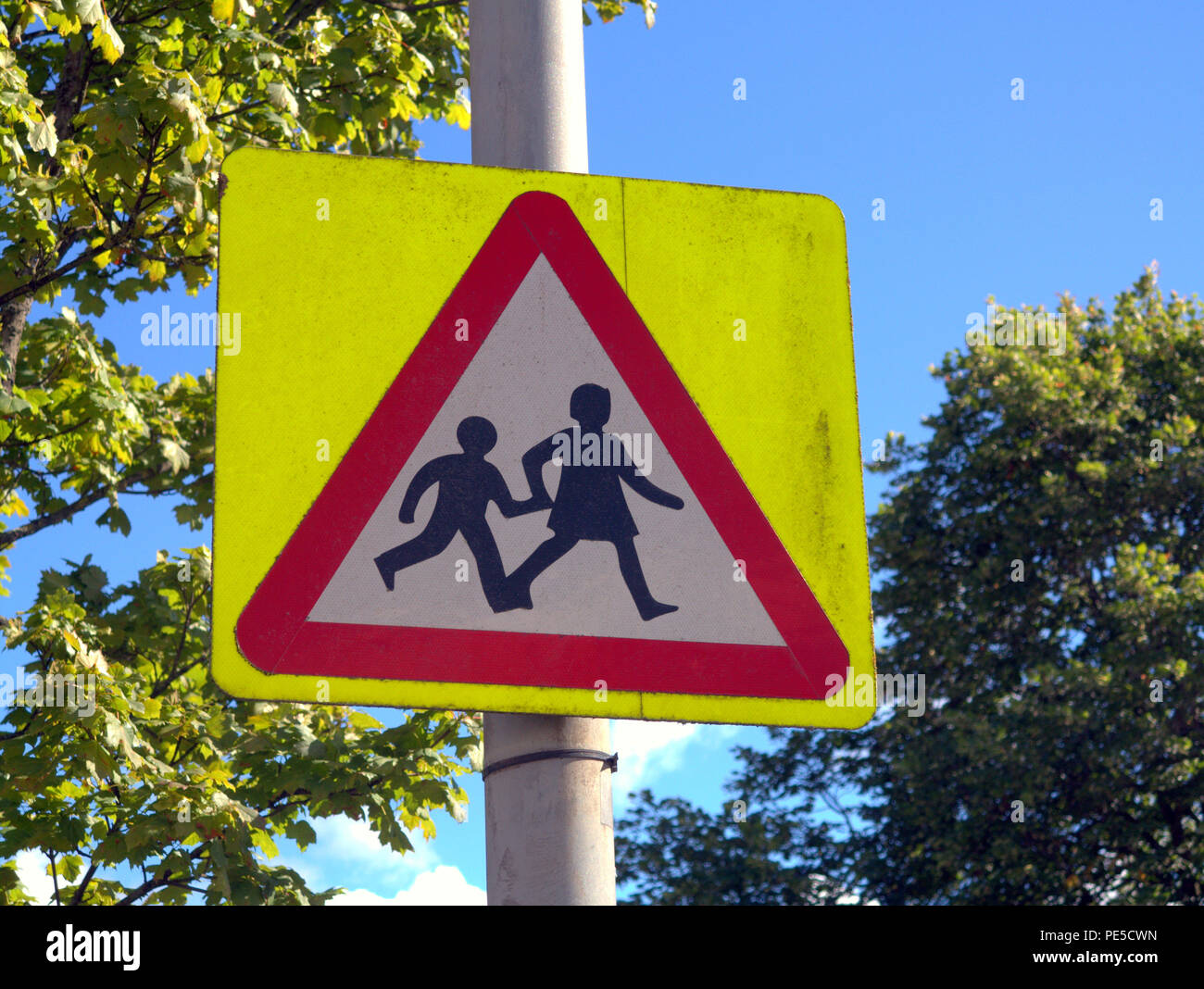 British road sign  schoolchildren children  crossing road warning sign blue sky - Stock Image