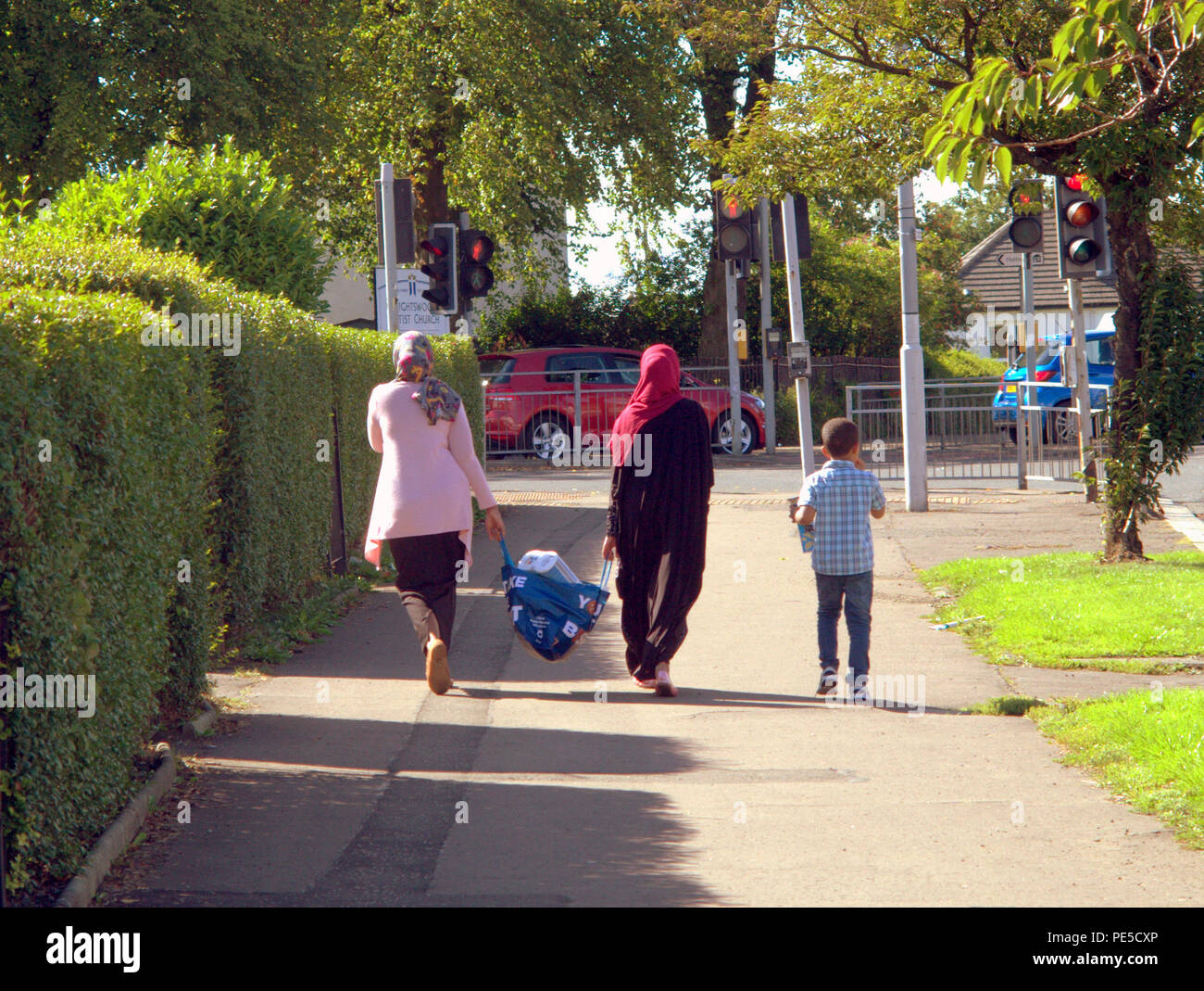 Muslims moslems family shopping bag hijab head gear walking on street family with child viewed from behind Glasgow, UK - Stock Image
