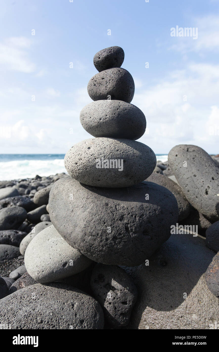 Stacked stones or pebbles on a beach with the blue sky in the background. - Stock Image