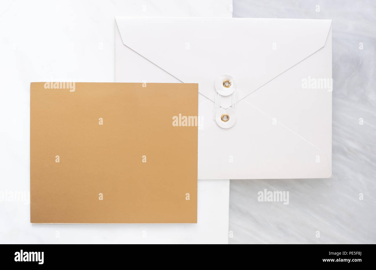 Top view of blank gold card overlap on white envelop on two layer step of marble table top.Mock up template for display of design .luxury business ite - Stock Image