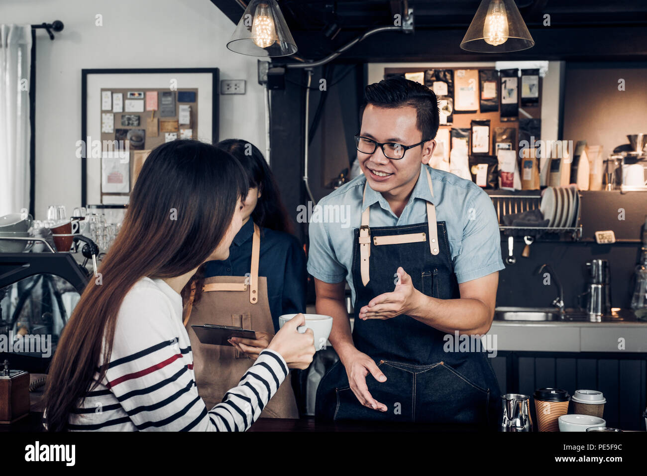 Male barista talking with customer about tasted of coffee cup with happy emotion at counter bar at cafe.coffee shop business owner concept,Service min - Stock Image