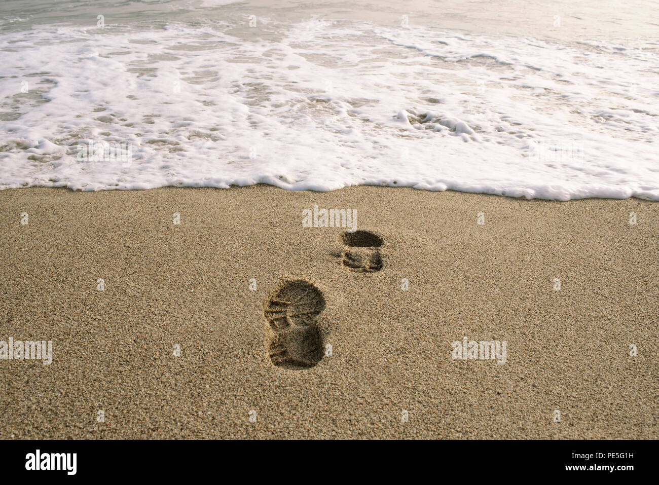 Swallowed by the sea. Conceptual image of shoe footprints in sand. Punta Hermosa, Peru. Jul 2018 - Stock Image
