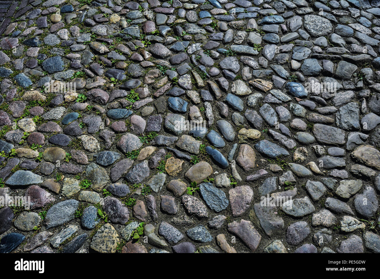 Ancient cobbled street surface close up showing all different stone sizes and colours used to cobble the surface. - Stock Image