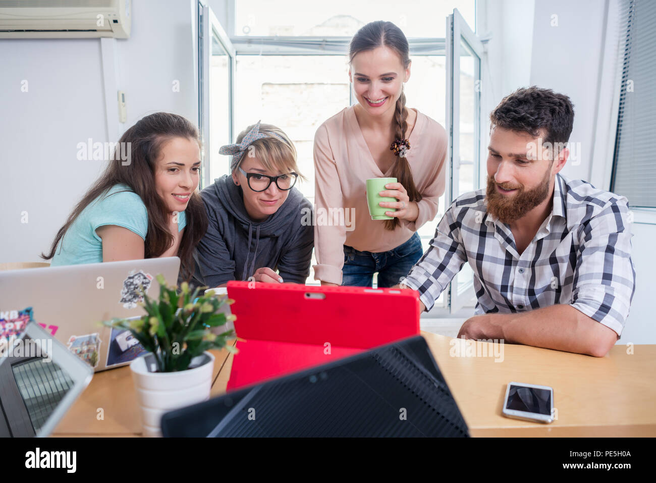 Four co-workers watching a business presentation in a modern shared office space - Stock Image