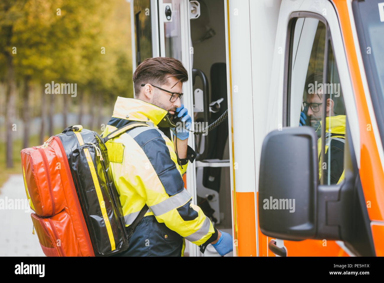 Emergency doctor using radio of ambulance - Stock Image