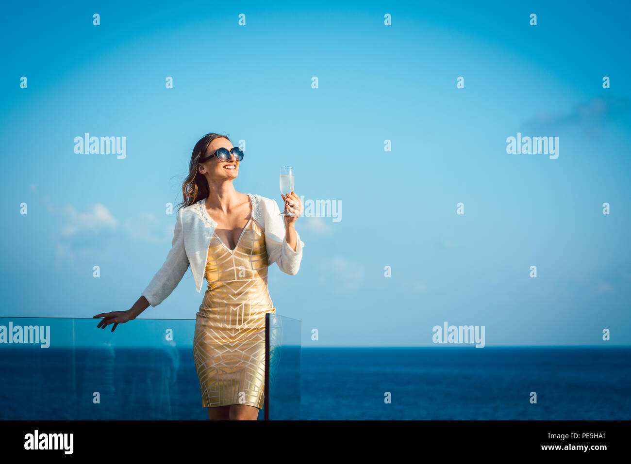 Woman drinking sparkling wine looking over ocean Stock Photo