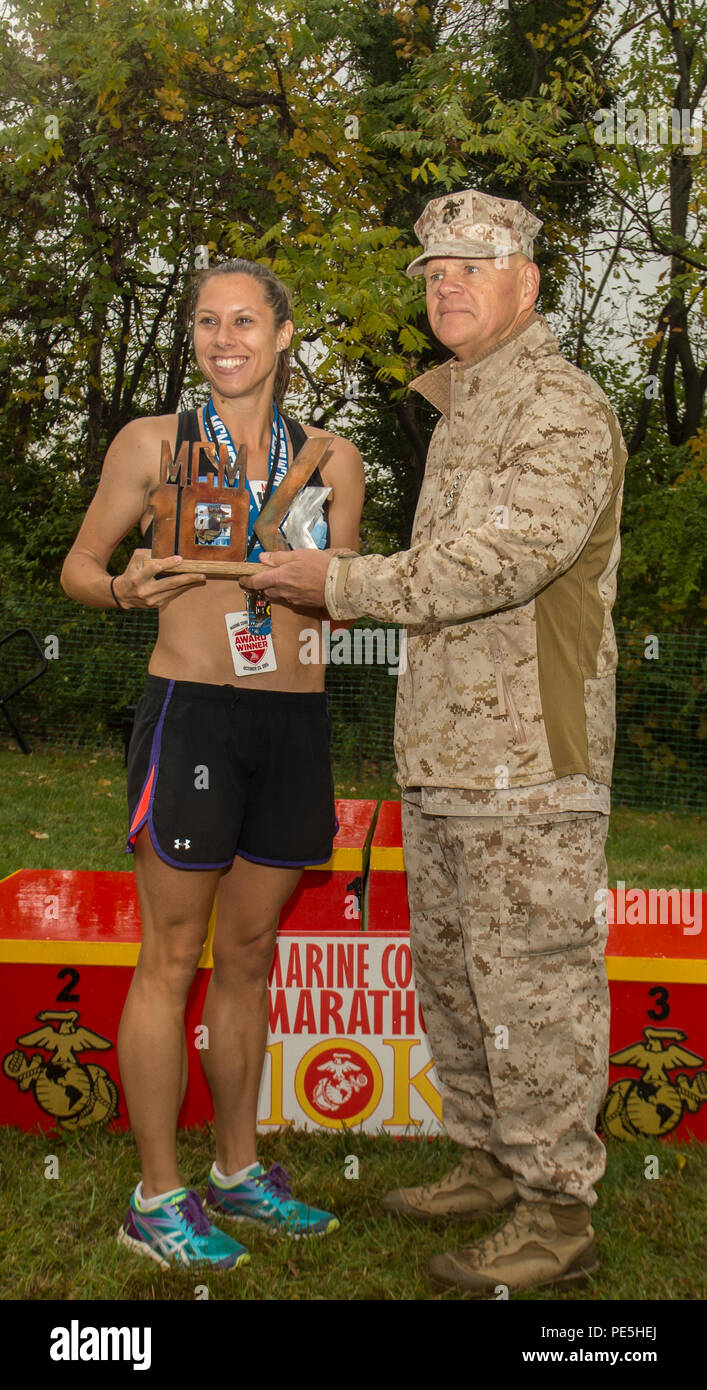 U.S. Marine Corps Commandant U.S. Marine Corps Gen. Robert Neller presents the 3rd place trophy to Sarah Bishop, of Fairfax, Va., at the 40th Annual Marine Corps Marathon, Arlington, Va., Oct. 25, 2015. Bishop finished the 10k portion of the marathon in 38 minutes and 13 seconds. (U.S. Marine Corps photo by Lance Cpl. Elisha N. Peake/Released) Stock Photo