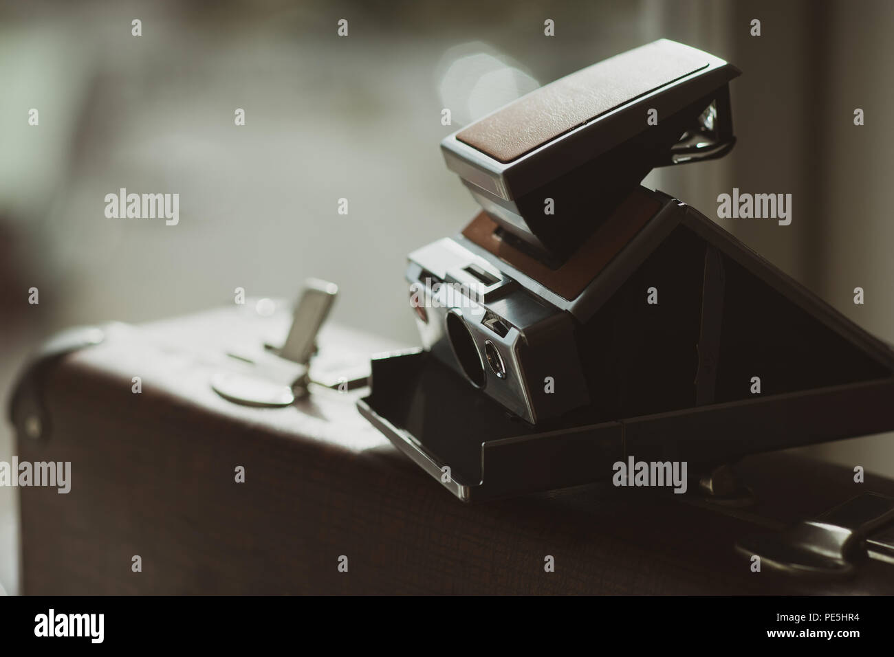 Vintage snapshot camera on an old suitcase with an open lock Stock Photo