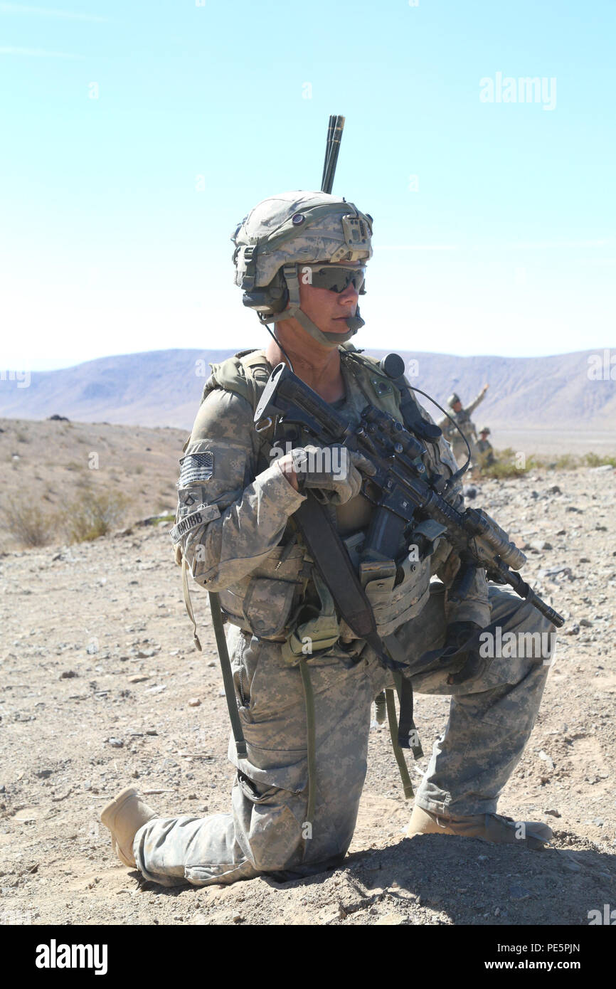 A U.S. Soldier from Charlie Company, 2nd Battalion, 23rd Infantry Regiment, 1st  Stryker Brigade Combat Team, 4th Infantry Division, scans for possible enemies during Decisive Action Rotation 15-10 at the National Training Center, Fort Irwin, Calif., Sept. 25, 2015. DA Rotations allow units to fully exercise their mission essential task list that supports the Army's core competencies: wide area security and combined arms maneuver. (U.S. Army photo by Spc. Michelle U. Blesam/ Released) - Stock Image