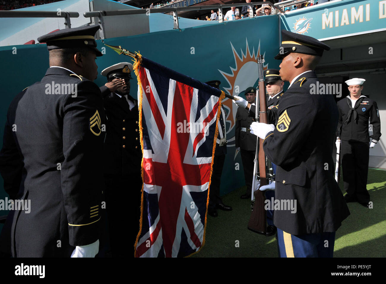U.S. service members with the RAF Molesworth Honor Guard assist members of the U.K. Color Guard with uncasing the Union Flag before the start of the International Series, Miami Dolphins versus New York Jets NFL game at Wembly Stadium, London October 4, 2015. Military personnel from the United Kingdom and the United States joined together for the performance of the national anthems of both countries during the NFL games in London. (U.S. Air Force photo by Staff Sgt. Ashley Hawkins/Released) - Stock Image