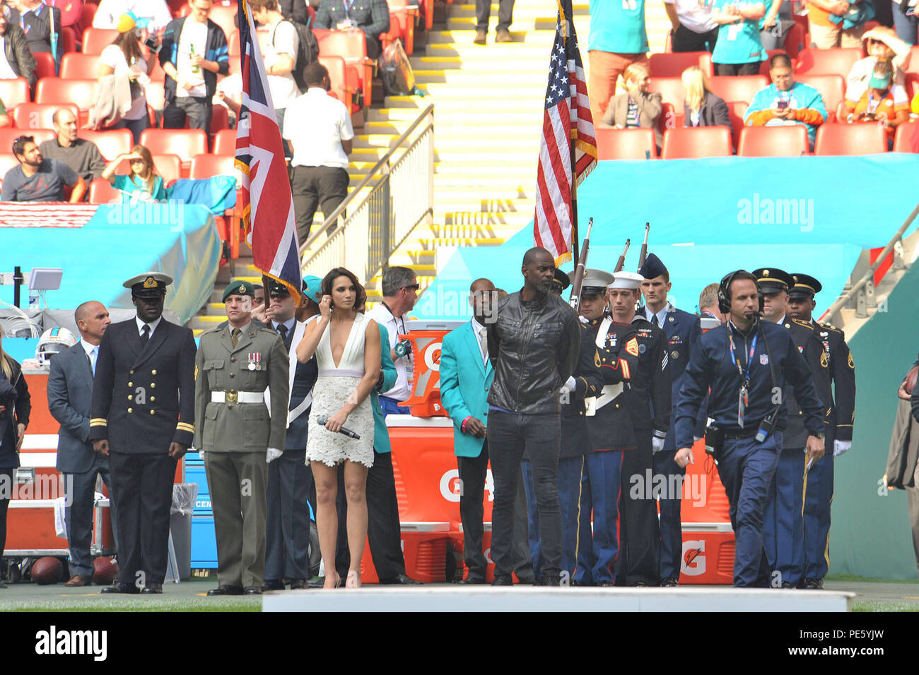 British opera singer Laura Wright, and American rhythm and blues singer Brian McKnight prepare to sing their countries' national anthems before the start of the International Series, Miami Dolphins versus New York Jets NFL game at Wembly Stadium, London October 4, 2015. Military personnel from the United Kingdom and the United States presented the national flags for the performance of the anthems during the NFL games in London. (U.S. Air Force photo by Staff Sgt. Ashley Hawkins/Released) - Stock Image