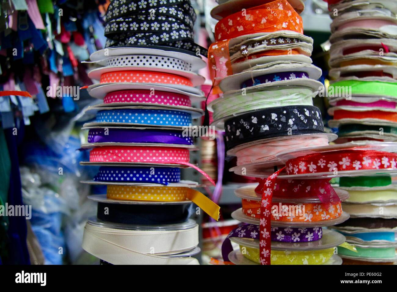 Stacks of multicoloured ribbons of various widths, patterns and textures in a craft market - Stock Image