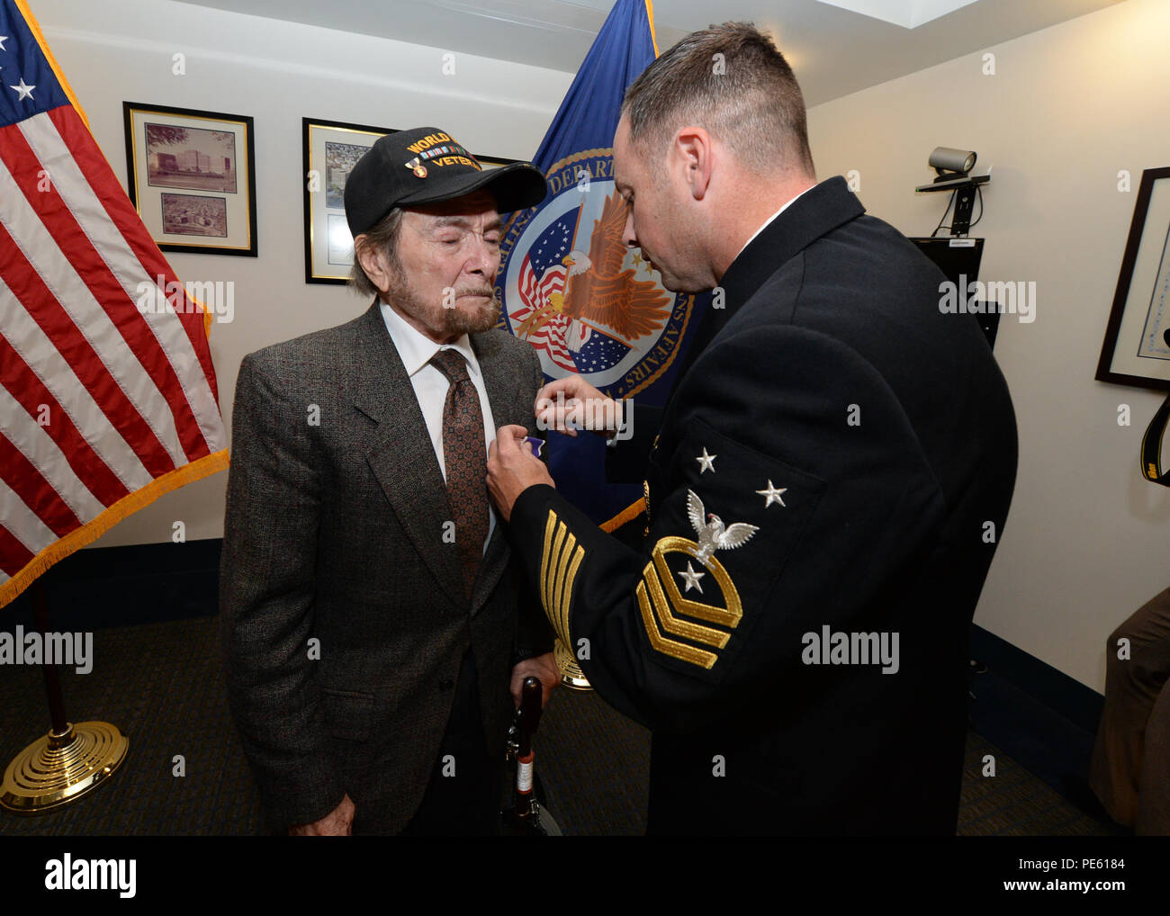 151005-N-PX557-027  PROVIDENCE, R.I.(Oct. 5, 2015) Leonard Harten, former U.S. Navy Soundman and survivor of the attacks that sank the Navajo-class tug USS Nauset (AT-89) during World War II, is presented with the Purple Heart by Command Master Chief Benjamin Pierson, assigned to U.S. Naval War College in Newport, Rhode Island.  Harten enlisted in the Navy on Nov. 14, 1942, and reported to Nauset following completion of Soundman school. On Sept. 9, 1943, while conducting operations in the Gulf of Salerno, a bomb from enemy aircraft exploded in close proximity to Nauset setting her ablaze. As a - Stock Image