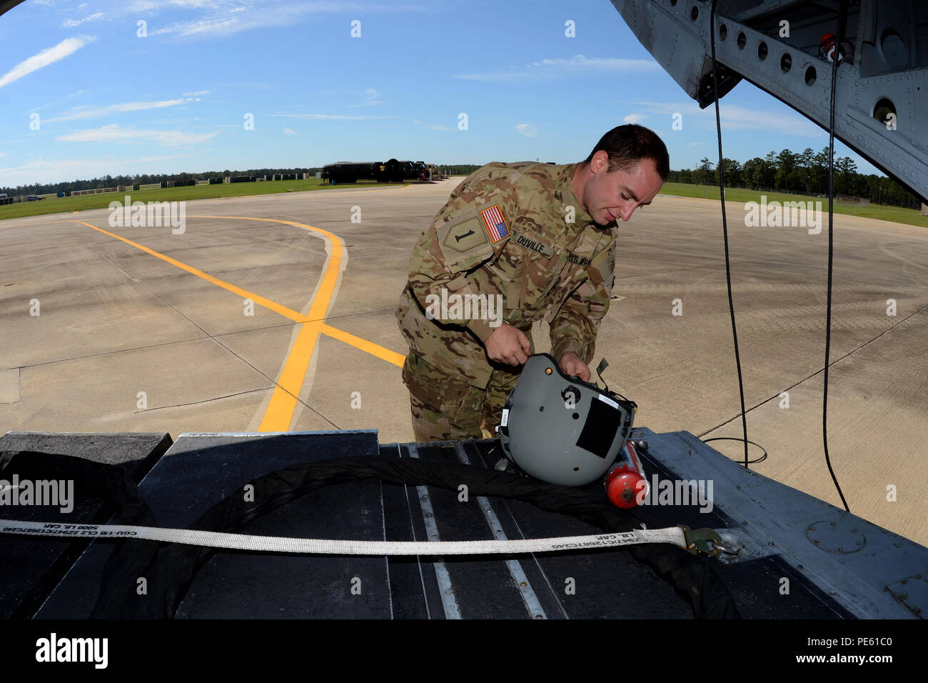 U.S. Army Spc. Ira Duville, a maintainer and crew chief with the South Carolina Army National Guard's 2-238th Aviation Detachment 1, performs pre-flight checks for a sling-loading mission on a Boeing CH-47 Chinook helicopter at McEntire Joint National Guard Base, S.C., during a statewide flood response, Oct. 6, 2015. The South Carolina National Guard has been activated to support state and county emergency management agencies and local first responders as historic flooding impacts counties statewide. Currently, more than 2,200 South Carolina National Guard members have been activated in respon Stock Photo