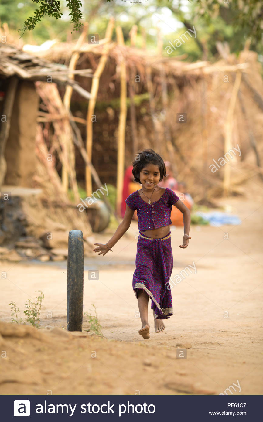 SARUPGANJ, RAJASTHAN, INDIA - JAN 09, 2017 ; An unidentified Indian girl playing with old tyre in Village and happy to poses for camera, Sarupganj, Ra - Stock Image