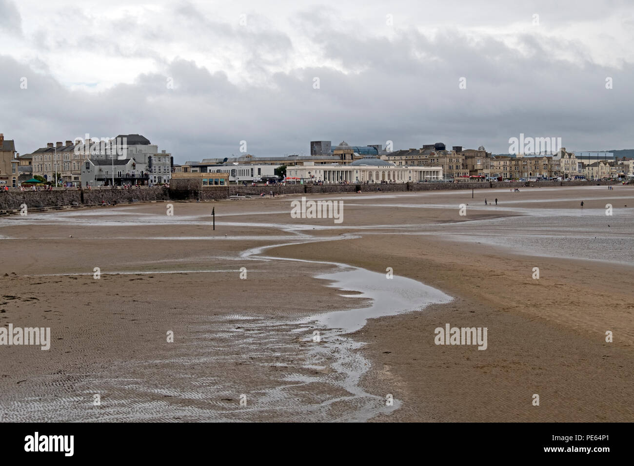 Weston-super-Mare, UK. 12th August, 2018. UK weather: after many hours of rain, a dry but overcast and breezy Sunday afternoon failed to bring many holidaymakers onto the beach, with some of those who did venture out wearing coats. Keith Ramsey/Alamy Live News - Stock Image