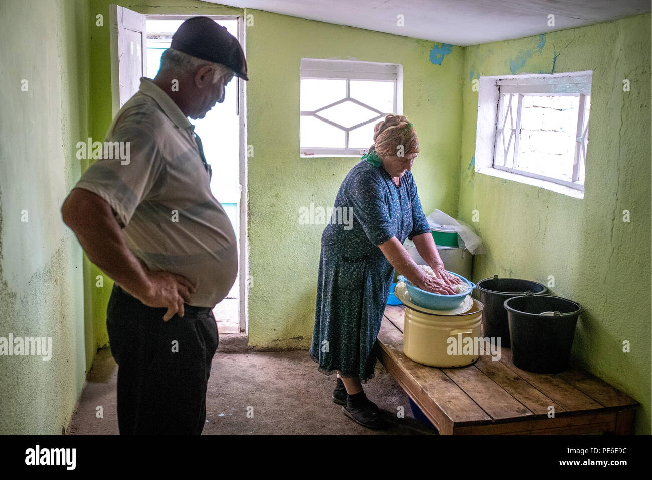 South Ossetia. 11th Aug, 2018. SOUTH OSSETIA - AUGUST 11, 2018: Margarita Madzigova, 63, and her husband Alikhan make home cheese in the village of Khetagurovo, Tskhinvali District, South Ossetia; they have been running a farm since their house was restored after the 2008 South Ossetian-Georgian military conflict. Sergei Bobylev/TASS Credit: ITAR-TASS News Agency/Alamy Live News - Stock Image