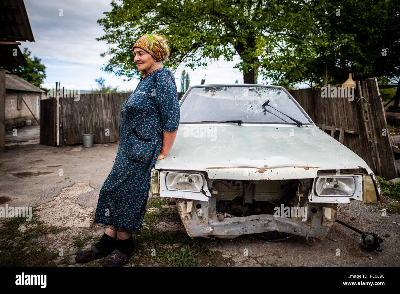 South Ossetia. 11th Aug, 2018. SOUTH OSSETIA - AUGUST 11, 2018: Margarita Madzigova, 63, poses standing by a car damaged in the 2008 South Ossetian-Georgian military conflict, in the village of Khetagurovo, Tskhinvali District, South Ossetia; Margarita and her husband Alikhan have been running a farm since their house was restored after the conflict. Sergei Bobylev/TASS Credit: ITAR-TASS News Agency/Alamy Live News - Stock Image