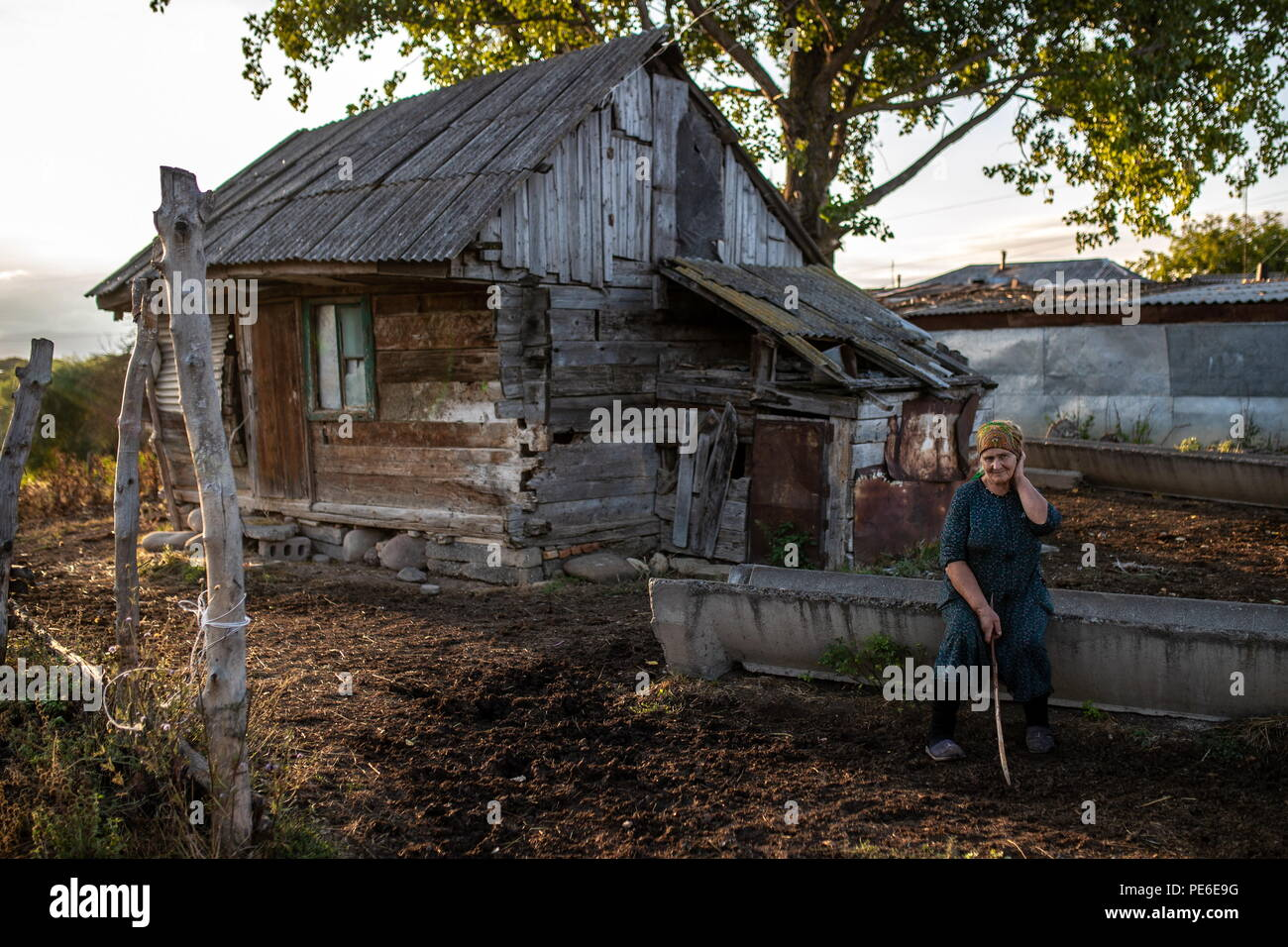 South Ossetia. 12th Aug, 2018. SOUTH OSSETIA - AUGUST 12, 2018: Margarita Madzigova, 63, poses outside her house in the village of Khetagurovo, Tskhinvali District, South Ossetia; Margarita and her husband Alikhan have been running a farm since their house was restored after the 2008 South Ossetian-Georgian military conflict. Sergei Bobylev/TASS Credit: ITAR-TASS News Agency/Alamy Live News - Stock Image