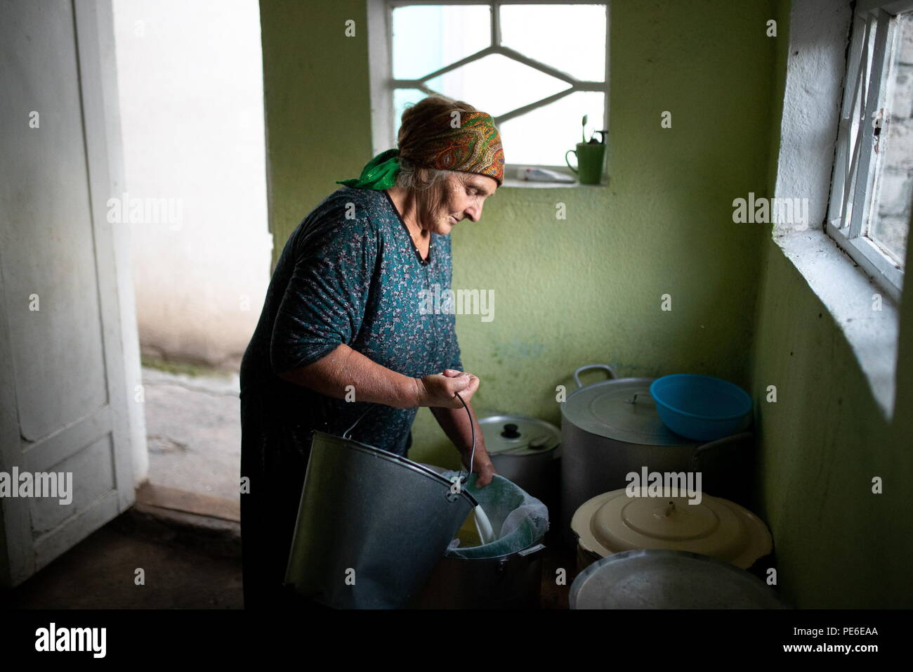 South Ossetia. 12th Aug, 2018. SOUTH OSSETIA - AUGUST 11, 2018: Margarita Madzigova, 63, makes home cheese in the village of Khetagurovo, Tskhinvali District, South Ossetia; Margarita and her husband Alikhan have been running a farm since their house was restored after the 2008 South Ossetian-Georgian military conflict. Sergei Bobylev/TASS Credit: ITAR-TASS News Agency/Alamy Live News - Stock Image