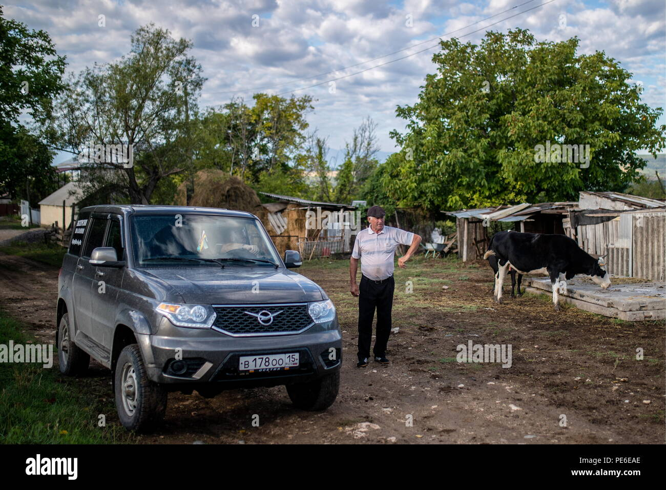 South Ossetia. 11th Aug, 2018. SOUTH OSSETIA - AUGUST 11, 2018: Alikhan Madzigov outside his house in the village of Khetagurovo, Tskhinvali District, South Ossetia; Alikhan and his wife Margarita, 63, have been running a farm since their house was restored after the 2008 South Ossetian-Georgian military conflict. Sergei Bobylev/TASS Credit: ITAR-TASS News Agency/Alamy Live News - Stock Image